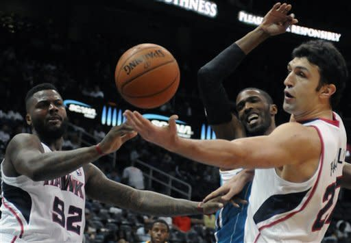 Atlanta Hawks' DeShawn Stevenson (92) teammate Zaza Pachulia (27) try to regain control of a rebound in front of New Orleans Hornets forward Hakim Warrick in the first half of an NBA basketball game in Atlanta, Thursday, Oct. 18, 2012. (AP Photo/David Tulis)