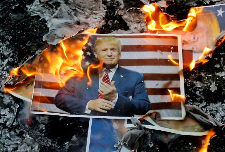 A burning portrait of US President Donald Trump on the ground during a demonstration in Tehran on December 11, 2017