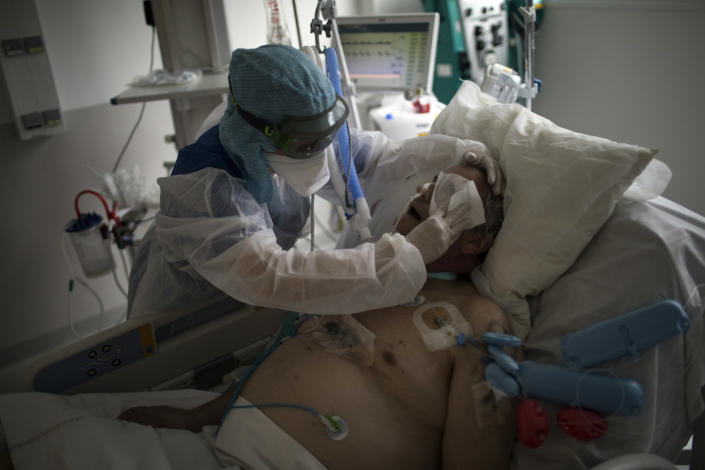 FILE - In this Feb. 2, 2021, file photo, a nurse cleans a patient suffering from COVID-19 in the ICU at the La Timone hospital in Marseille, southern France. The global death toll from the coronavirus topped a staggering 3 million people Saturday, April 17, 2021, amid repeated setbacks in the worldwide vaccination campaign and a deepening crisis in places such as Brazil, India and France. (AP Photo/Daniel Cole, File)