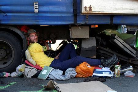 A climate change activist is glued on a truck during the Extinction Rebellion protest on Waterloo Bridge in London, Britain April 20, 2019. REUTERS/Simon Dawson
