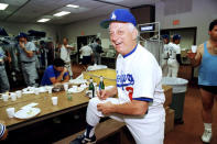 FILE - Los Angeles Dodgers manager Tommy Lasorda autographs a baseball in the Dodgertown locker-room in Vero Beach, Fla., in this Wednesday, Feb. 15, 1990, file photo. Tommy Lasorda, the fiery Hall of Fame manager who guided the Los Angeles Dodgers to two World Series titles and later became an ambassador for the sport he loved during his 71 years with the franchise, has died. He was 93. The Dodgers said Friday, Jan. 8, 2021, that he had a heart attack at his home in Fullerton, California. Resuscitation attempts were made on the way to a hospital, where he was pronounced dead shortly before 11 p.m. Thursday. (AP Photo/Richard Drew, File)