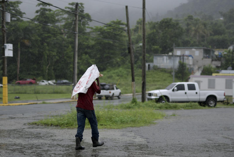 A man uses a flour bag to protect himself from the rain, in Yabucoa, Puerto Rico, Tuesday, Sept. 24, 2019. Tropical Storm Karen regained strength as it swirled toward Puerto Rico, where it's expected to bring heavy rains and strong winds. (AP Photo/Carlos Giusti)