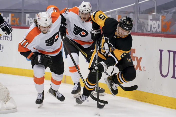 Pittsburgh Penguins' Mike Matheson (5) tries to control the puck as Philadelphia Flyers' Travis Konecny (11) and Connor Bunnaman (82) pursue during the second period of an NHL hockey game, Tuesday, March 2, 2021, in Pittsburgh. (AP Photo/Keith Srakocic)