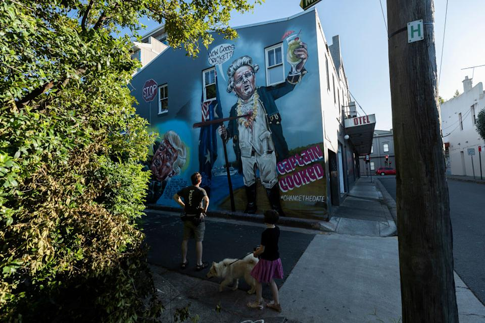 People look at a mural by street artist Scott Marsh in Newtown early on Australia Day. Source: Getty