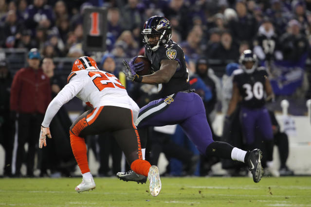 Baltimore Ravens running back Gus Edwards, right, rushes past Cleveland Browns strong safety Damarious Randall in the first half of an NFL football game, Sunday, Dec. 30, 2018, in Baltimore. (AP Photo/Carolyn Kaster)