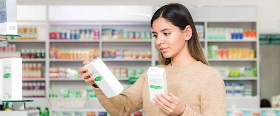woman choosing vitamins and supplements in a grocery store.