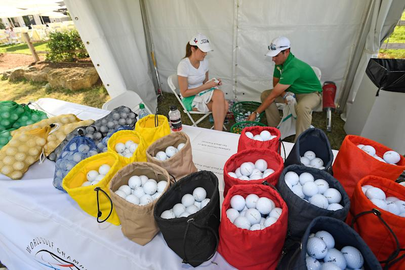 Volunteers sort practice balls near the range during the first round of the WGC-Dell Technologies Match Play.