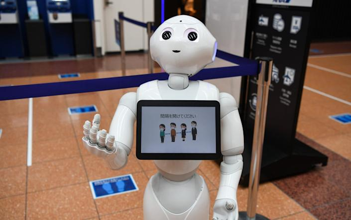 A SoftBank Group Corp. Pepper humanoid robot reminds travelers to social distance at an All Nippon Airways Co. (ANA) check-in area at Haneda Airport in Tokyo, Japan, on Tuesday, June 28, 2020. Concern over the virus situation in Japan in growing as cases have surged in recent weeks. An outbreak initially thought confined to nighttime entertainment areas in Tokyo has spread to workplaces and across the country. Photographer: Noriko Hayashi/Bloomberg - Bloomberg