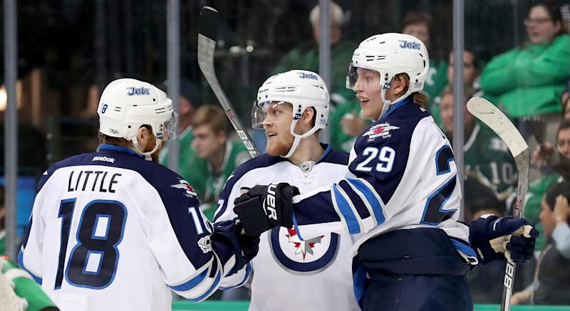 Winnipeg's Nikolaj Ehlers (#27) celebrates with Patrik Laine (#29) and Bryan Little (#18) after scoring against the Dallas Stars in February 2017. (Photo by Tom Pennington/Getty Images)