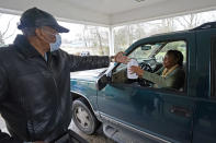 James Spiva, a member of New Mt. Zion Missionary Baptist Church, left, hands out a bottle of hand sanitizer and reusable face masks to a resident, Monday, March 1, 2021, at a Jackson, Miss., water distribution site on the church's parking lot. Non-potable water as well as bottled water was provided for area residents and was being distributed at seven sites in Mississippi's capital city — more than 10 days after winter storms wreaked havoc on the city's water system because the system is still struggling to maintain consistent water pressure, authorities said. (AP Photo/Rogelio V. Solis)