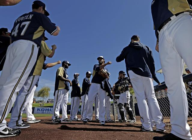 Players high five Milwaukee Brewers' Yovani Gallardo before his start of an exhibition spring training baseball game against the Chicago White Sox Monday, March 10, 2014, in Phoenix. (AP Photo/Morry Gash)