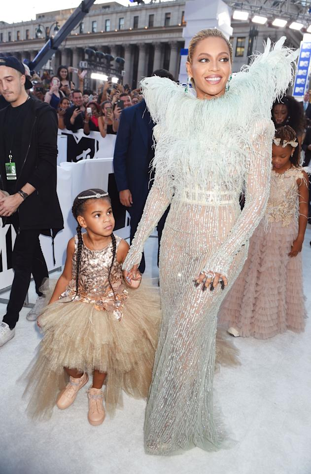 <p>Beyoncé, who confirmed at the last minute that she's performing, chose a look from Francesco Scognamiglio's Fall 2016 couture collection covered in sequins and featuring feather wings. She brought along daughter Blue Ivy, wearing a shiny top and massive tutu skirt with pink sneakers and hair extensions, as her date, and both looked like fairies from a far-off fashionable land. <i>(Photo: Getty Images)</i></p>