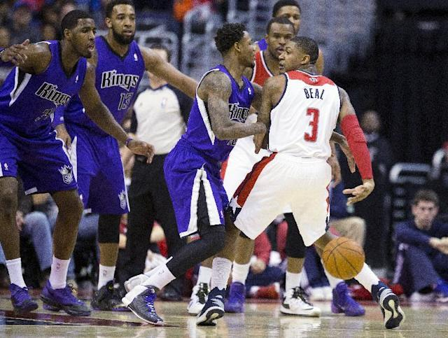 Washington Wizards shooting guard Bradley Beal, right, throws a pass behind his back to elude Sacramento Kings defenders, from left, power forward Jason Thompson, power forward Derrick Williams, and shooting guard Ben McLemore during the first half of an NBA basketball game on Sunday, Feb. 9, 2014, in Washington. (AP Photo/ Evan Vucci)