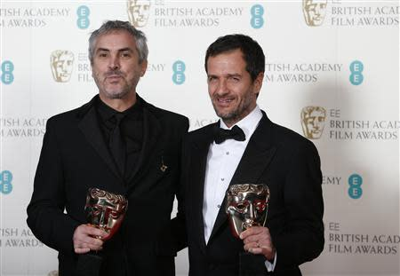 "Director Alfonso Cuaron (L) and producer David Heyman celebrate after winning Outstanding British Film for ""Gravity"" at the Royal Opera House in London February 16, 2014. REUTERS/Suzanne Plunkett"