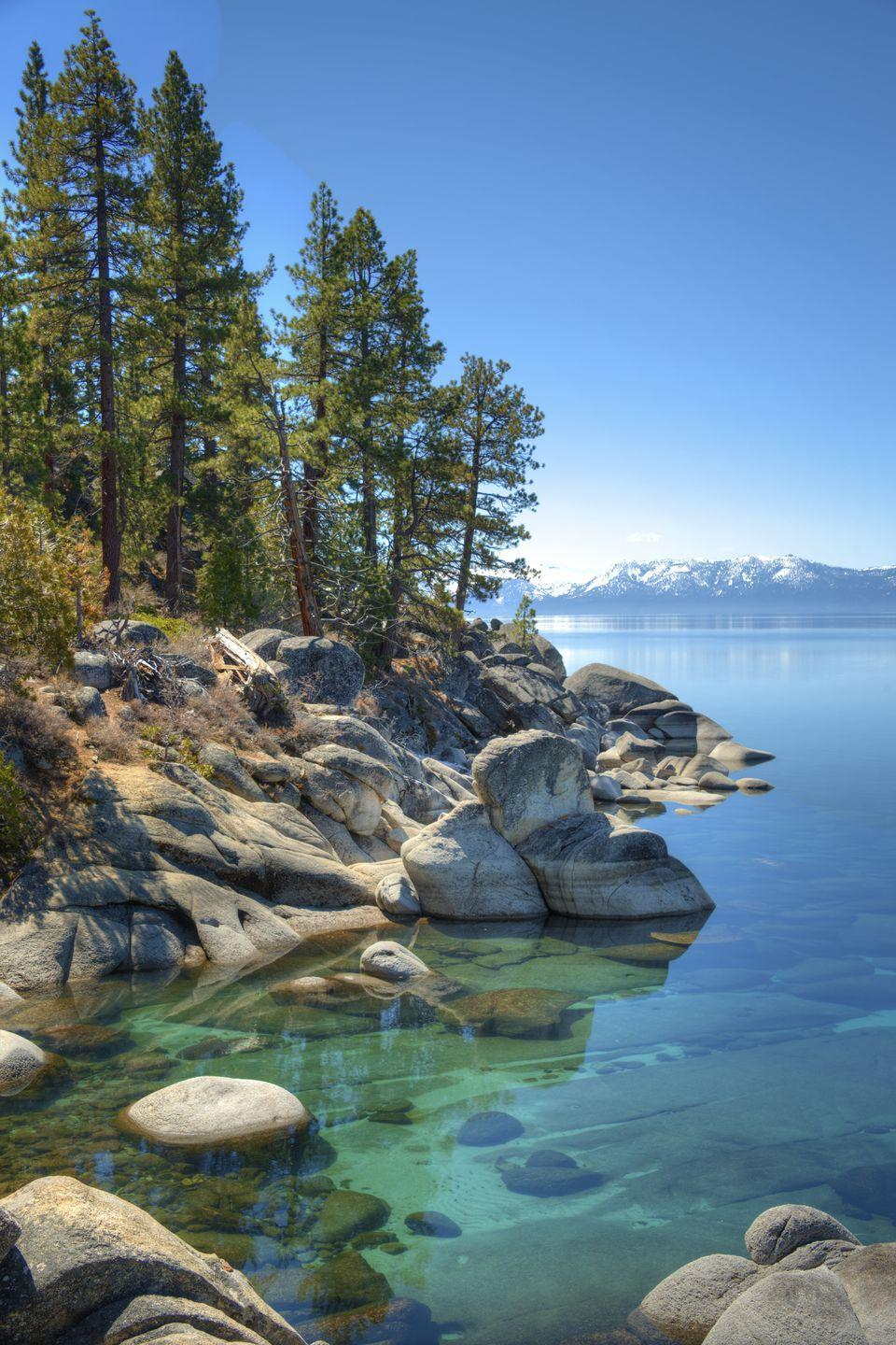 """<p><strong>Where: </strong>Lake Tahoe, California and Nevada</p><p><strong>Why We Love It: </strong>Surrounded by the Sierra Nevada Mountains on all sides, Lake Tahoe's waters are so clear you can see 70 feet deep.</p><p><strong>RELATED:</strong> <a href=""""https://www.countryliving.com/life/travel/g4459/most-beautiful-lakes-in-america/"""" rel=""""nofollow noopener"""" target=""""_blank"""" data-ylk=""""slk:The 50 Most Beautiful Lakes in America"""" class=""""link rapid-noclick-resp"""">The 50 Most Beautiful Lakes in America</a></p>"""