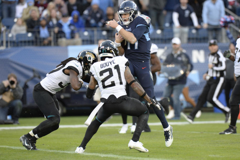 Tennessee Titans quarterback Ryan Tannehill (17) jumps over Jacksonville Jaguars cornerback A.J. Bouye (21) as Tannehil scores a touchdown on a 21-yard run in the first half of an NFL football game Sunday, Nov. 24, 2019, in Nashville, Tenn. (AP Photo/Mark Zaleski)