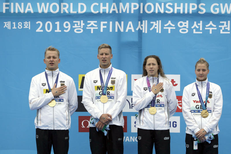 Members of the gold medal-winning team from Germany stand with their medals after the 5km mixed relay open water swim at the World Swimming Championships in Yeosu, South Korea, Thursday, July 18, 2019. (AP Photo/Mark Schiefelbein)