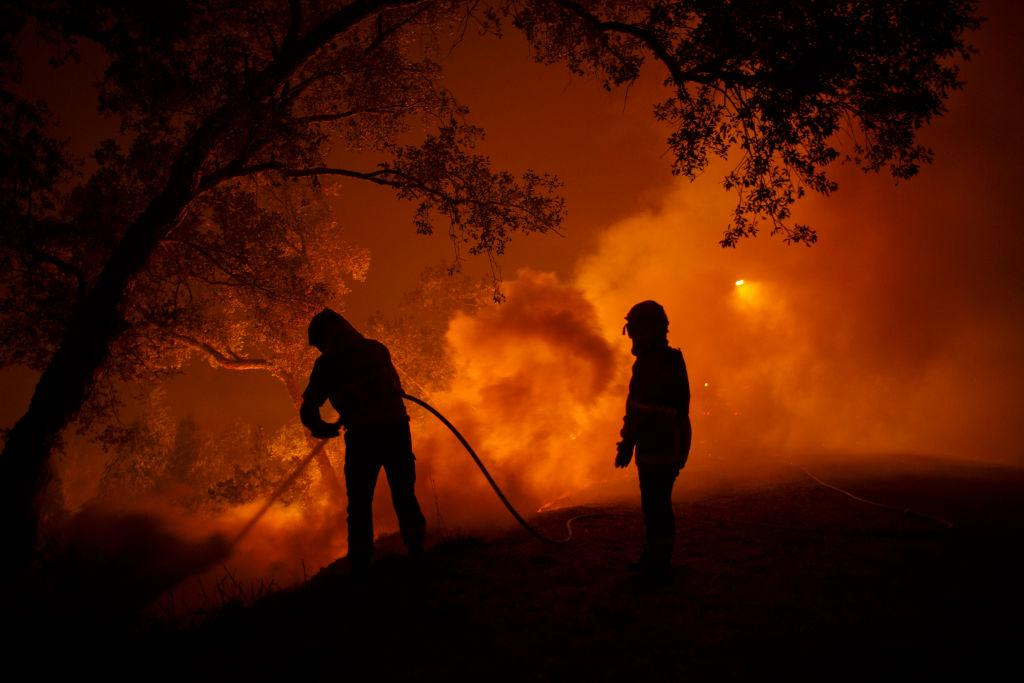 <p>Firefighters battle a forest wildfire next to Vilarinho village, near Lousa in Coimbra region, Portugal. At least 36 people have died in fires in Portugal and four others in Spain as Ophelia winds were hitting the North West of the Iberian Peninsule. (Pablo Blazquez Dominguez/Getty Images) </p>