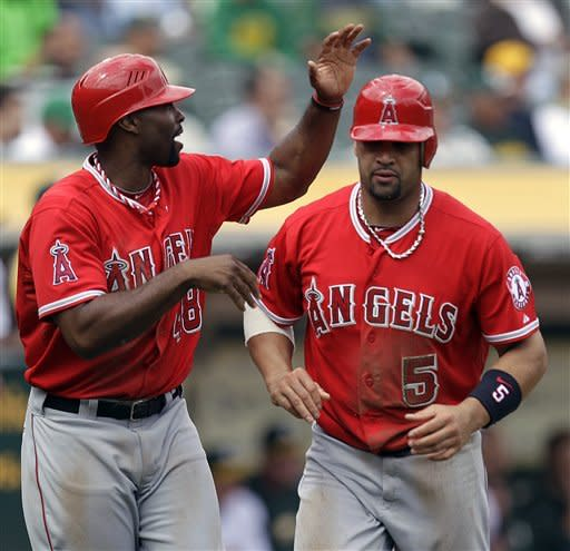 Los Angeles Angels' Torii Hunter, left, and Albert Pujols (5) celebrate after scoring against the Oakland Athletics' in the third inning of a baseball game on Wednesday, Sept. 5, 2012, in Oakland, Calif. Both scored on a single by Angels' Howie Kendrick. (AP Photo/Ben Margot)