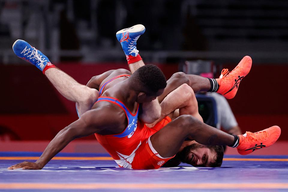 <p>Cuba's Jeandry Garzon Caballero (red) wrestles Belarus' Mahamedkhabib Kadzimahamedau in their men's freestyle 74kg wrestling early round match during the Tokyo 2020 Olympic Games at the Makuhari Messe in Tokyo on August 5, 2021. (Photo by Jack GUEZ / AFP)</p>