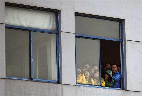 Workers on strike watch from a window of Hi-P International factory during a protest in Shanghai December 2, 2011.