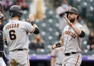 San Francisco Giants' Steven Duggar, left, waits to congratulate Brandon Belt as he crosses home plate after hitting a three-run home run in the first inning of game one of a baseball doubleheader Tuesday, May 4, 2021, in Denver. (AP Photo/David Zalubowski)