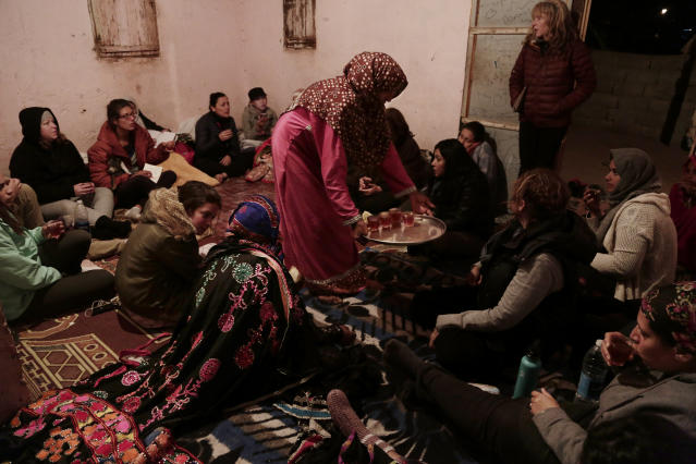 In this March 30, 2019 photo, Umm Yasser offers tea to during a women's only circle of tourists and Bedouin from the Hamada tribe, at her home in Wadi Sahw, Abu Zenima, in South Sinai, Egypt. Four Bedouin women are for the first time leading tours in Egypt's Sinai Peninsula, breaking new ground in their deeply conservative community, where women almost never work outside the home or interact with outsiders. The women guide groups of female tourists through the stunning mountain landscapes, part of a Bedouin-led project of hiking tours in southern Sinai. (AP Photo/Nariman El-Mofty)