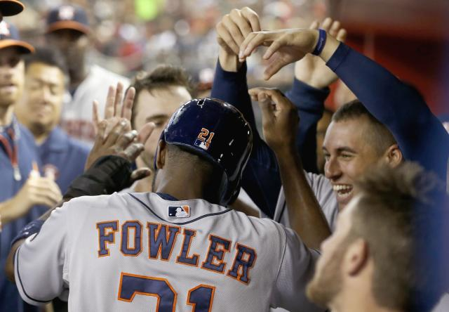 Houston Astros' Dexter Fowler, left, celebrates his run scored against the Arizona Diamondbacks with teammates, including George Springer, top right, during the second inning of a baseball game on Monday, June 9, 2014, in Phoenix. (AP Photo/Ross D. Franklin)