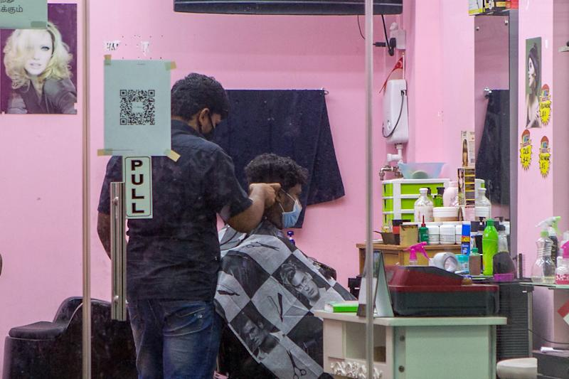 A man in a face mask seen getting a haircut at a barbershop in Little India. (PHOTO: Dhany Osman / Yahoo News Singapore)