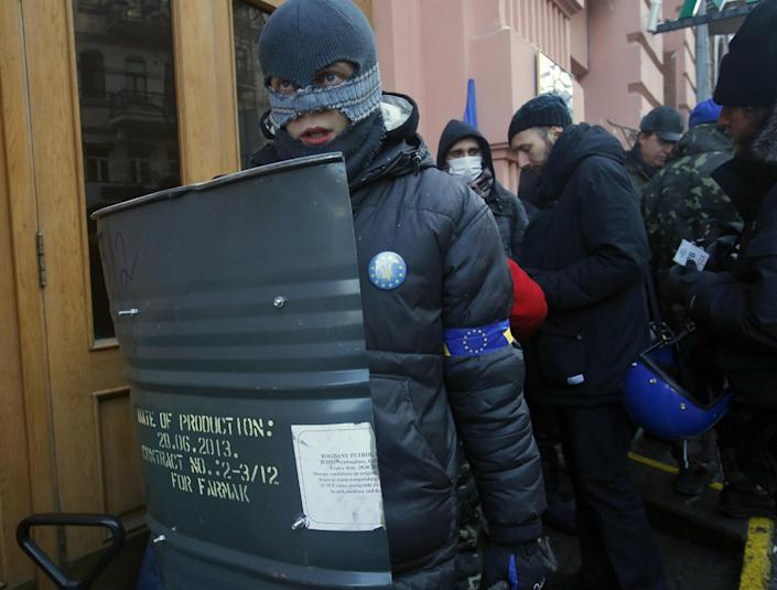 Protesters stand guard outside the Justice Ministry in central Kiev, Ukraine, Monday, Jan. 27, 2014. Ukraine's justice minister is threatening to call for a state of emergency unless protesters leave her ministry building, which they occupied during the night. The seizure of the building early Monday underlined how anti-government demonstrators are increasingly willing to take dramatic action as they push for the president's resignation and other concessions. (AP Photo/Sergei Grits)