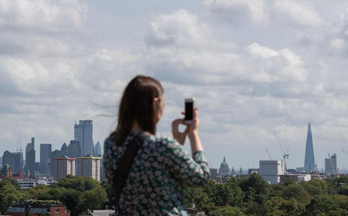 A woman takes a photo of the London skyline from Primrose Hill in London on Saturday (Picture: PA)