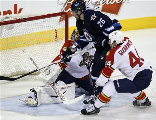 A shot by Winnipeg Jets' Blake Wheeler (26) goes off the crossbar behind Florida Panthers goaltender Jacob Markstrom (35) during the first period of their NHL hockey game in Winnipeg, Manitoba, Thursday, April 11, 2013. (AP Photo/The Canadian Press, John Woods)