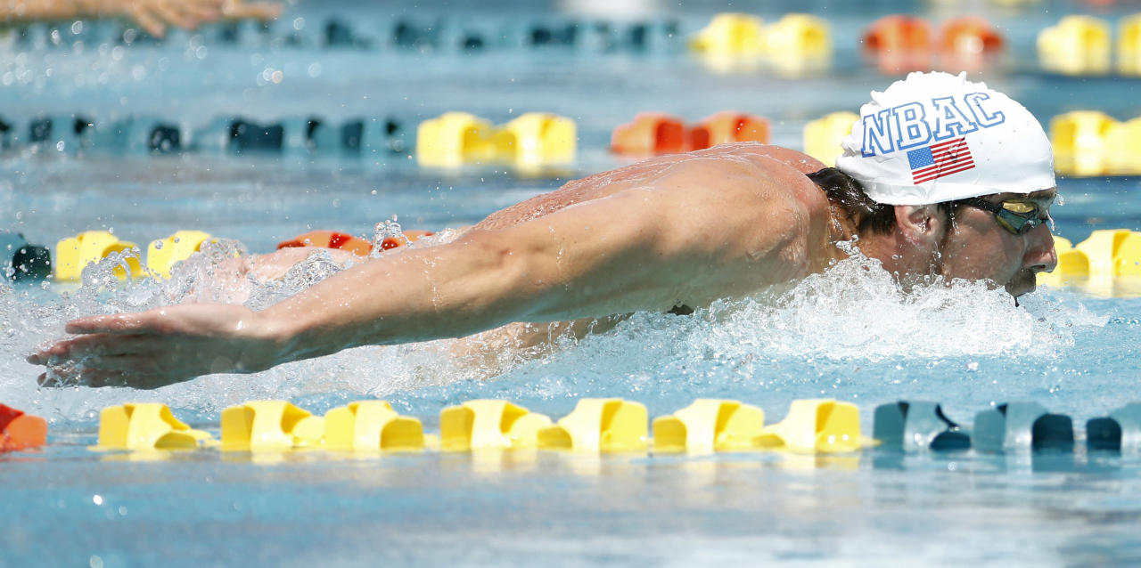 Michael Phelps competes in the 100-meter butterfly during the Arena Grand Prix swim meet, Thursday, April 24, 2014, in Mesa, Ariz. It is Phelps' first competitive event after a nearly two-year retirement. (AP Photo/Matt York)