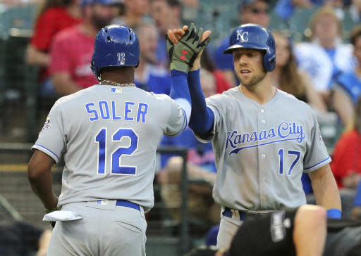 Kansas City Royals' Jorge Soler (12) high-fives Hunter Dozier (17) after a solo home run against the Texas Rangers during the fourth inning of a baseball game Friday, May 25, 2018, in Arlington, Texas. (AP Photo/Richard W. Rodriguez)