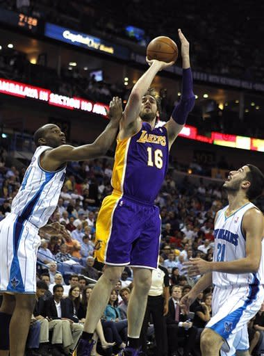 Los Angeles Lakers power forward Pau Gasol (16) shoots between New Orleans Hornets power forward Carl Landry, left, and point guard Greivis Vasquez (21) in the first half of an NBA basketball game in New Orleans, Monday, April 9, 2012. (AP Photo/Gerald Herbert)