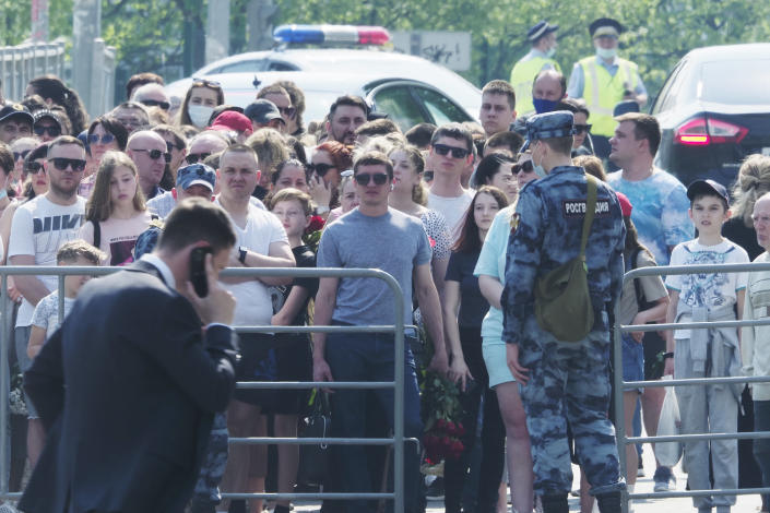 People gather to lay flowers near a school after a shooting on Tuesday in Kazan, Russia, Wednesday, May 12, 2021. Russian officials say a gunman attacked a school in the city of Kazan and Russian officials say several people have been killed. Officials said the dead in Tuesday's shooting include students, a teacher and a school worker. Authorities also say over 20 others have been hospitalised with wounds. (AP Photo/Dmitri Lovetsky)