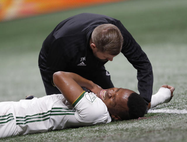 Portland Timbers forward Jeremy Ebobisse (17) is checked by a member of the medical staff after being injured during the first half of the MLS Cup championship soccer game against Atlanta United, Saturday, Dec. 8, 2018, in Atlanta. (AP Photo/John Bazemore)