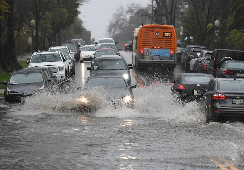 Cars drive through a flooded street on Saturday after a storm dumped heavy rain in Los Angeles.