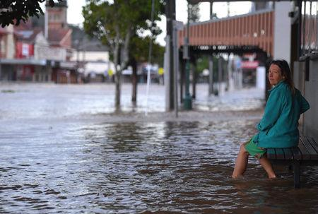 A local resident watches as floodwaters enter the main street of northern New South Wales town of Lismore, Australia, after heavy rains associated with Cyclone Debbie swelled rivers to record heights across the region