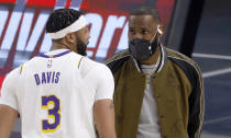Los Angeles Lakers forward Anthony Davis (3) and forward LeBron James (23) talk during a timeout as the Lakers play the Dallas Mavericks during the first half of an NBA basketball game Saturday, April 24, 2021, in Dallas. James is not playing due to an injury. (AP Photo/Ron Jenkins)