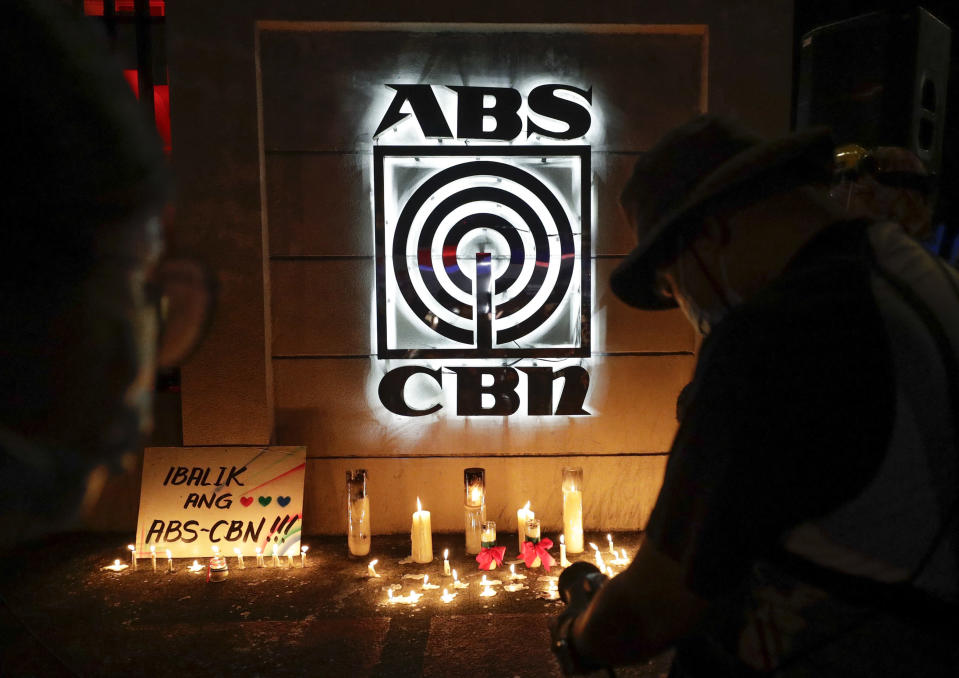 """Supporters of ABS-CBN take photos of candles outside their headquarters in Quezon City, Philippines, Friday July 10, 2020. Philippine lawmakers voted Friday to reject the license renewal of the country's largest TV network ABS-CBN, shutting down a major news provider that had been repeatedly threatened by the president over its critical coverage. Sign reads """"Bring back ABS-CBN"""".(AP Photo/Aaron Favila)"""