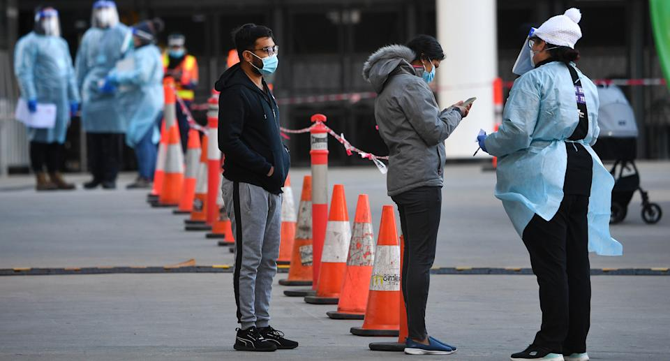 A healthcare worker is seen speaking to people waiting in line outside of a pop-up Covid19 testing facility outside of the LaCrosse apartment block in Docklands, Melbourne, Sunday, July 25, 2021. Source: AAP