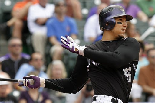 Colorado Rockies' Carlos Gonzalez hits a two-run home run against Los Angeles Dodgers starting pitcher Clayton Kershaw during the eighth inning of a baseball game, Wednesday, May 2, 2012, in Denver. The Rockies won 8-5. (AP Photo/Barry Gutierrez)