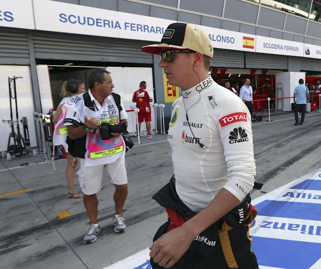 Lotus driver Kimi Raikkonen of Finland walks by Ferrari pits during the third free practice for the Italian Formula One Grand Prix at the Monza racetrack, in Monza, Italy, Saturday, Sept. 7, 2013. The Formula one race will be held on Sunday. (AP Photo/Luca Bruno)