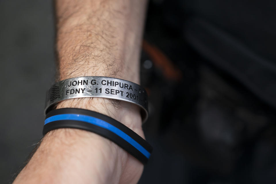 """NYPD officer Michael Dougherty, a 25-year veteran, displays a bracelet bearing the name of John G. Chipura, an FDNY firefighter and former Marine who died responding to the attacks, as he stands beside the south reflecting pool of the 9/11 Memorial & Museum where names of his deceased colleagues and friends are displayed, Monday, Aug. 16, 2021, in New York. """"He was a good guy,"""" said Dougherty. """"That means a lot. If you're in the service, you know that means he was special."""" A foundation in Chipura's name hosts an annual golf outing that was derailed due to the COVID-19 pandemic last year. (AP Photo/John Minchillo)"""