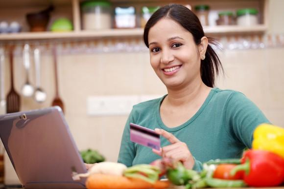 Woman with credit card in front of a laptop