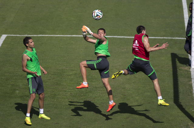 Mexico's national soccer team players Javier Hernandez, center, fight for the ball with Hector Herrera, right, as Diego Reyes looks on during a training session in Santos, Brazil, Sunday, June 8, 2014. Mexico play in group A of the 2014 soccer World Cup. (AP Photo/Eduardo Verdugo)