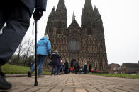 Members of the public queue to receive a dose of the Oxford/AstraZeneca coronavirus vaccine at Lichfield Cathedral, in Staffordshire, England, Friday, Jan. 15, 2021. The U.K. is ramping up its mass vaccination program as the government seeks to protect the country's oldest and most vulnerable residents before easing a third national lockdown. (Jacob King/PA via AP)