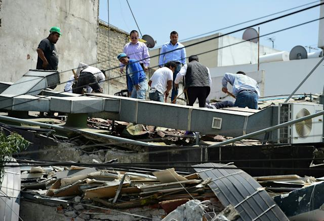 People look through the debris of a building.