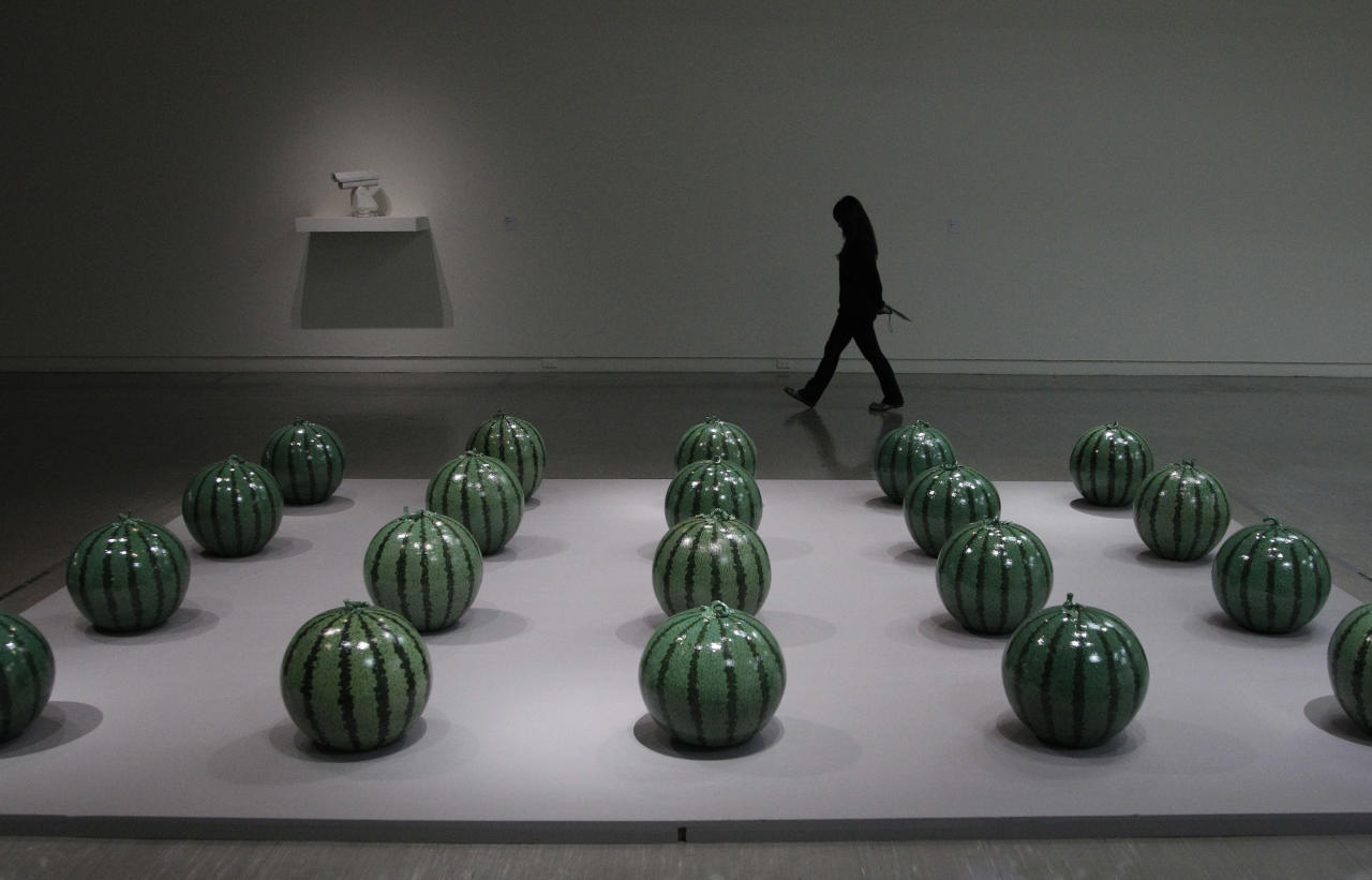 "A visitor passes an instillation entitled ""Watermelon"" by the Chinese artist and activist Ai Weiwei at the ""Ai Weiwei is Absent"" exhibition in the Taipei Fine Arts Museum in Taipei, Taiwan, Friday, Oct. 28, 2011. The exhibition opens Oct. 29 and will run for three months. (AP Photo/Wally Santana)"